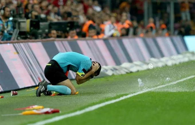 Trợ lý trọng tài ôm đầu ngã xuống sân vì bị CĐV ném đồ