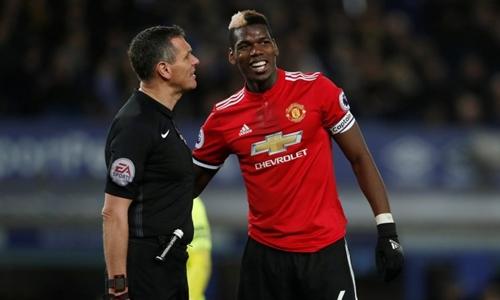 Pogba làm ngã trọng tài Marriner trong trận gặp Everton. Ảnh: PA.