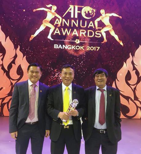 Ông Trần Quốc Tuấn (giữa) cầm danh hiệu Liên đoàn thành viên của năm ở hạng mục phát triển do AFC trao tặng.