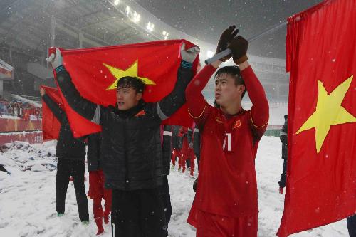 Duy Mạnh (phải) và lá cờ trước khi anh cắm trên sân Thường Châu. Ảnh: Anh Khoa.