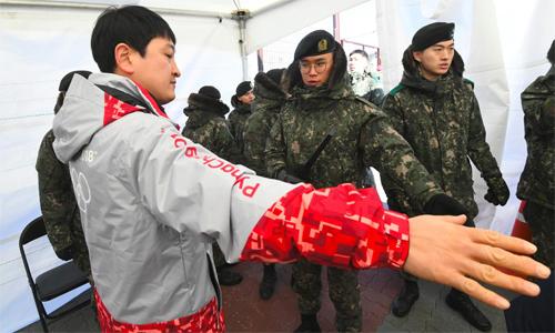 Quân đội được cử đến làng VĐV để thay thế công việc của các nhân viên bị nghi nhiễm virus. Ảnh: AFP.