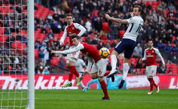 Kane đánh bại Koscielny trong pha không chiến dẫn đến bàn thắng duy nhất của trận đấu. Ảnh: Reuters.