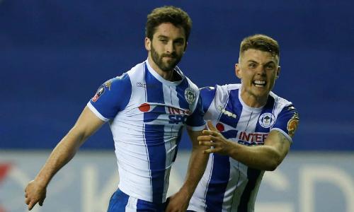 Tiền đạo của Wigan chia vui cùng đồng đội. Ảnh: Reuters.