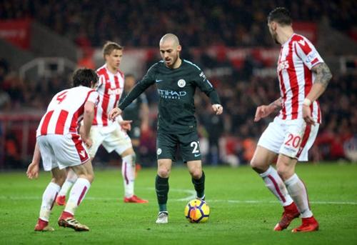 Silva giữa vòng vây cầu thủ Stoke. Ảnh: Reuters.