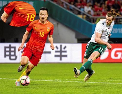 Tiền đạo Gao Linphải dùng băng, che các phần cơ thể có hình xăm, theo lệnh cấm từ CFA, trong trận đấu với Xứ Wales. Ảnh: Reuters.