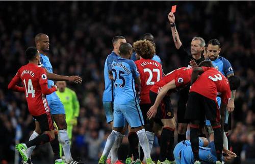 Trọng tài Atkinson rút thẻ đỏ với Fellaini ở trận derby Manchester mùa giải trước. Ảnh:AFP.