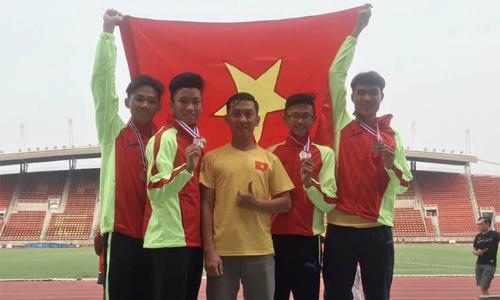 Lê Tiến Long (ngoài cùng bên phải) mừng HC vàng cùng các đồng đội và HLV. Ảnh: Điền kinh TP HCM.
