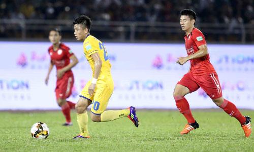 Các cầu thủ SLNA (áo vàng) dễ dàng đi bóng trước các cầu thủ chủ nhà TP HCM. Ảnh: Anh Khoa.