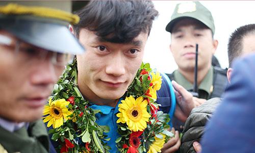 Thủ môn Bùi Tiến Dũng được bảo vệ nghiêm ngặt khi về tới sân bay Nội Bài. Ảnh: Đức Đồng.