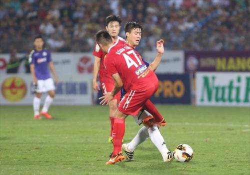 Tăng Tiến vào bóng nguy hiểm với Duy Mạnh trong trận đá bù vòng 3 V-League 2018.