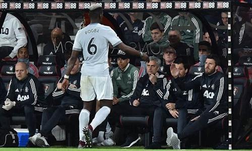 Pogba chủ động giơ tay chào hỏi ban huấn luyện Man Utd. Ảnh: REX.