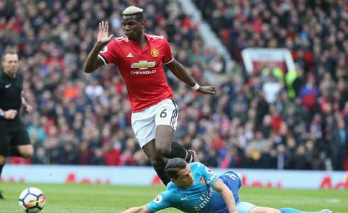 Pogba qua người sau cú vào bóng của Xhaka. Ảnh:AFP.