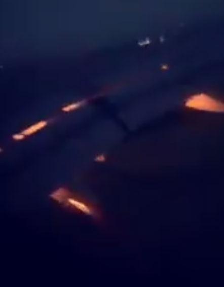 Cảnh động cơ phụt lửa được một cầu thủ ghi lại qua cửa sổ máy bay.