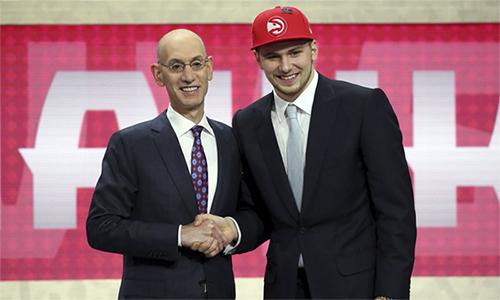 Luka Doncic đội mũ Hawks khi được chọn, nhưng cuối cùng thuộc về Mavericks. Anh được kỳ vọng sẽ là Dirk Nowzitki mới tại Dallas. Ảnh: AP.
