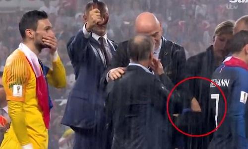 Nữ quan chức cho huy chương vào túi trong lúc nói chuyện với Tổng thống Putin. Ảnh: Sun.