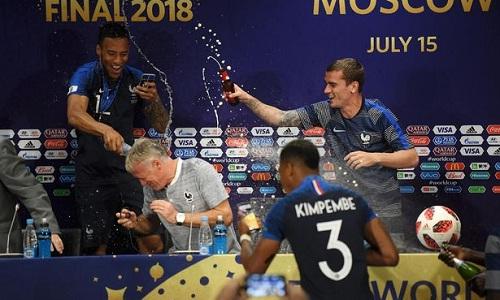 Deschamps bị các học trò đổ champagne lên người trong phòng họp báo. Ảnh: FIFA.