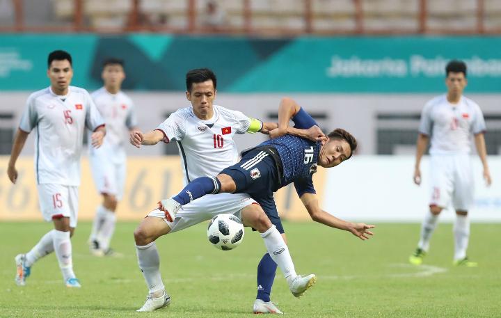 Đội trưởng Văn Quyết tranh bóng quyệt liệt với các cầu thủ Olympic Nhật Bản trong trận cầu chiều nay, 19/8. Ảnh: Đức Đồng.