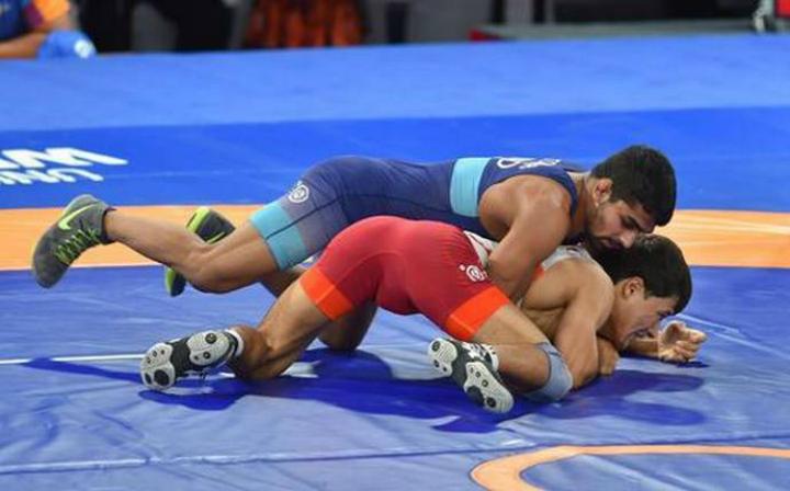 Rustem (áo đỏ) bị đánh bại ở trận đấu đầu tiên bởiSandeep Tomar của Ấn Độ ở nội dung vật tự do 57 kg. Ảnh:PTI.