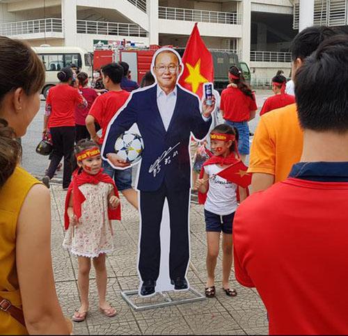 Trẻ em Việt Nam tạo dáng chụp hình với ảnh của HLV Park Hang-seo. Ảnh: Yonhap.