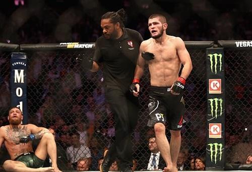 McGregor ngồi bệt xuống sàn đấu để thở, sau khi để Khabib khóa cổ ở hiệp bốn. Ảnh: Reuters.