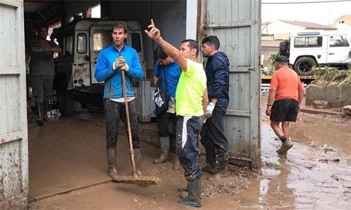 Nadal mang ủng, cầm chổi giúp người dândọn dẹp sau trận lụt. Ảnh: Marca.