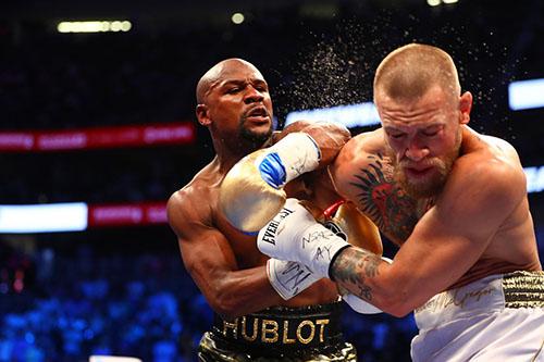 Mayweather (quầnd đen) từng thắng dễ dàng một võ sĩ UFC là McGregor hồi năm 2017, theo luật quyền Anh. Ảnh: Reuters.