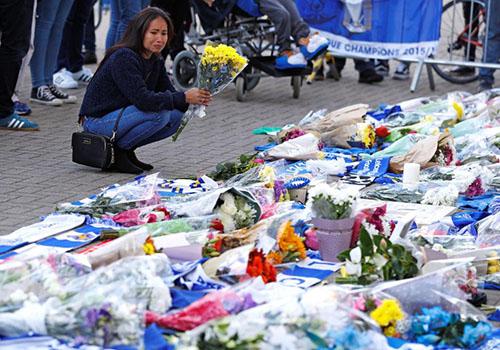 Một CĐV Leicester vừa cầm hoa vừa khóc bên ngoài sân King Power. Ảnh: Reuters.