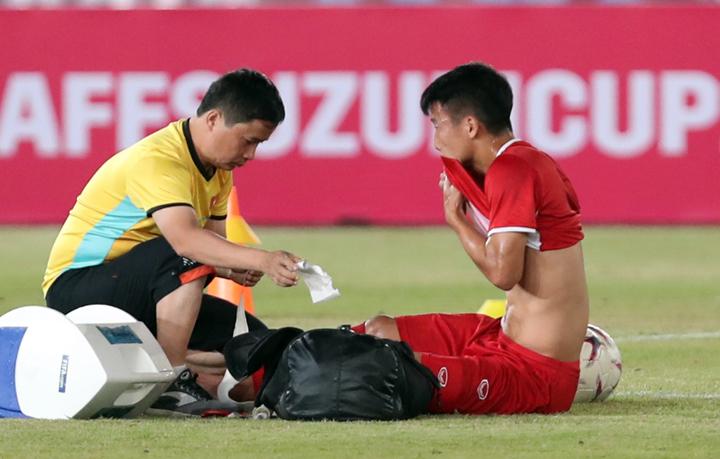Trung vệ Bùi Tiến Dũng được bác sĩ chăm sóc trong buổi tập trên sân vận động quốc gia Lào chiều 7/11. Ảnh: Đức Đồng