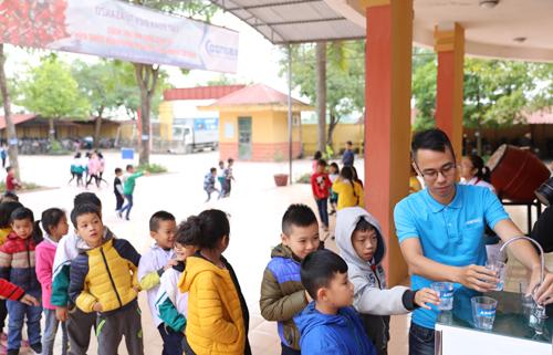 Học sinh trường Tiểu học Xuân Nộn xếp hàng uống nước từ máy lọc mới lắp.