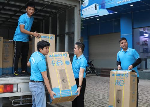 Ông Phạm Văn Tam (thứ ba từ phải sang) cùng đội ngũ Asanzo chất hàng lên xe chuẩn bị chở đến trường học.