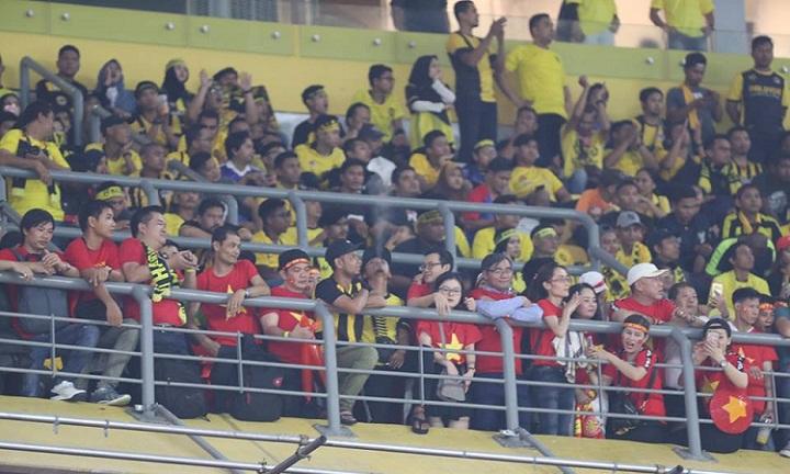 Một nhóm CĐV Việt Nam không có chỗ ngồi, đứng lẫn trong khu vực CĐV Malaysia. Ảnh: Lâm Thỏa.