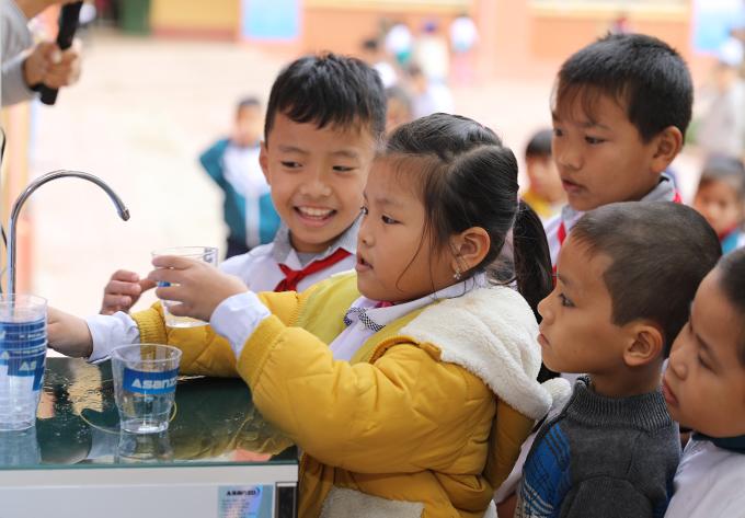Các em nhỏ tại trường Tiểu học Xuân Nộn, Đông Anhuống nước từ máy lọc nước mà Asanzo mới lắp đặt.