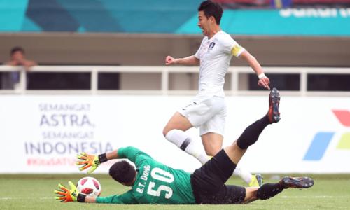 Son Heung Min đi bóng trước sự truy cản của thủ môn Bùi Tiến Dũng tại ASIAD 2018. Ảnh: Lâm Thỏa.