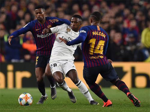 Vinicius giữa vòng vây của hai cầu thủ Barca trong trận lượt đi. Ảnh: Reuters
