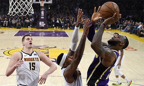James (áo xanh) không thể giúp Lakers thoát thua trước đội nhì bảng miền Tây Nuggets. Ảnh: AP.