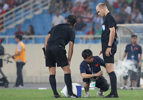 Bác sĩ của U23 Việt Nam xịt thuốc giảm đau cho ông Sherzod. Ảnh: Lâm Thoả.