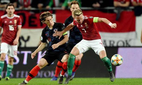 Modric (áo sẫm) tranh bóng với đội trưởng Hungary, Dzsudzsak. Ảnh: Reuters.