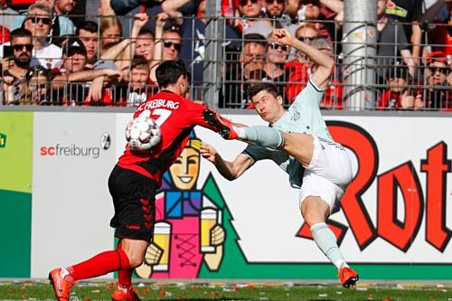 Lewandowski tung người dứt điểm gỡ hòa cho Bayern. Ảnh:Reuters.