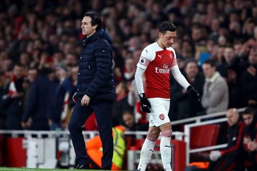 Emery (trái) bảo vệ Ozil trước trận gặp Napoli. Ảnh: EPA.