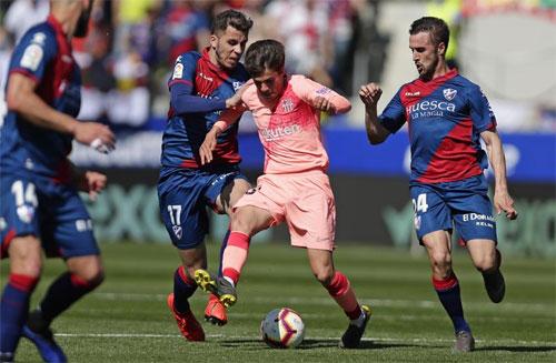 Tài năng trẻ Puig bị ba cầu thủ Huesca vây quanh.