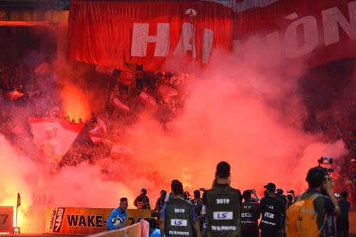 CĐV Hải Phòng ném pháo sáng xuống sân, khiến trận đấu bị gián đoạn tối 21/4. Ảnh: Giang Huy