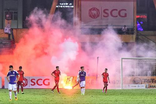Trọng tài phải cho tạm dừng trận đấu giữa Hà Nội và Hải Phòng ở cuối hiệp một vì CĐV khách ném pháo sáng xuống sân, ảnh hưởng tới khả năng thi đấu của cầu thủ. Ảnh: Giang Huy