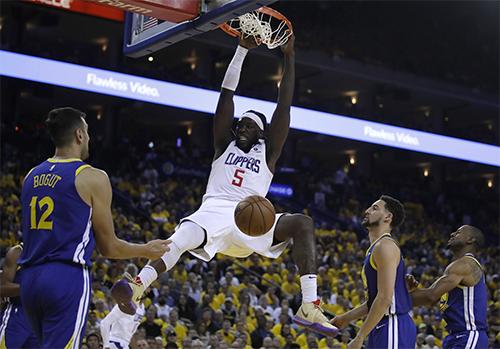 Harrell (trắng) giúp Clippers áp đảo Warriors ở khu vực dưới rổ. Ảnh: AP.