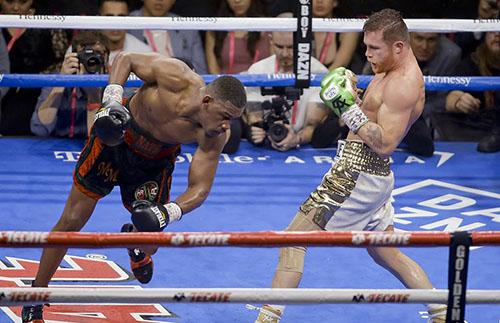 Jacobs (trái) trượt chân và ngã ra sàn đấu đầu hiệp 12. Ảnh: Reuters.