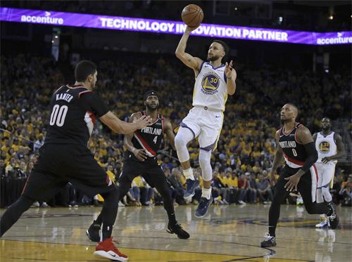 Curry (trắng) trong vòng vây của các cầu thủ phòng ngự Trail Blazers. Ảnh: AP.