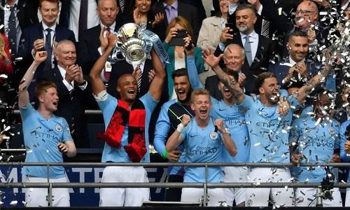 Kompany nângchiếc Cupthứ ba của Man City ở mùa này. Ảnh: Reuters.