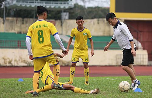 Văn Quyến (áo trắng) làm trợ lý cho HLV Phạm Như Thuật ở đội U15 SLNA. Ảnh: Báo Nghệ An.