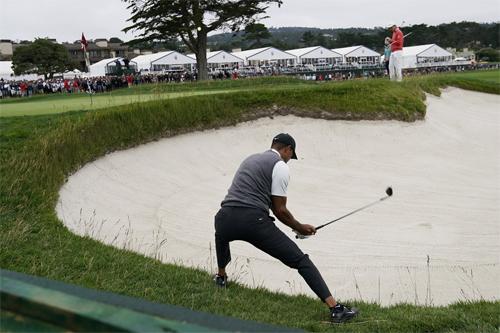 Tiger Woods vất vả cứu bóng từ bẫy cát ở hố cuối. Ảnh: AP.
