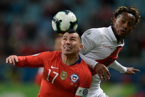 Medel (trái) tranh bóng với cầu thủ Peru. Ảnh: AFP.