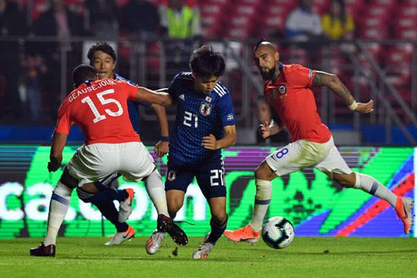 Trước các đàn anh Chile vượt trội về thể hình và kinh nghiệm thi đấu, Kubo (áo xanh) vẫn chơi tự tin. Ảnh: Reuters.
